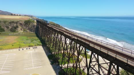 Vista-Aérea-Amtrak-Passenger-Train-Traveling-Along-The-Coast-Of-California-With-Pacific-Ocean-And-Gaviota-Trestle