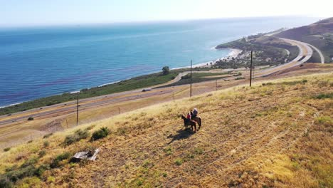 Beautiful-Aerial-Of-Retired-Retirement-Couple-Riding-Horses-Horseback-On-A-Ranch-Overlooking-The-Pacific-Ocean-In-Santa-Barbara-California-2