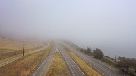 Antena-Sobre-Una-Autopista-Neblinosa-US-101-Pacific-Coast-Highway-Con-Tráfico-A-Lo-Largo-De-La-Costa-De-California