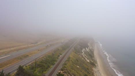 Antena-Sobre-Una-Autopista-Neblinosa-US-101-Pacific-Coast-Highway-Con-Tráfico-A-Lo-Largo-De-La-Costa-De-California-1