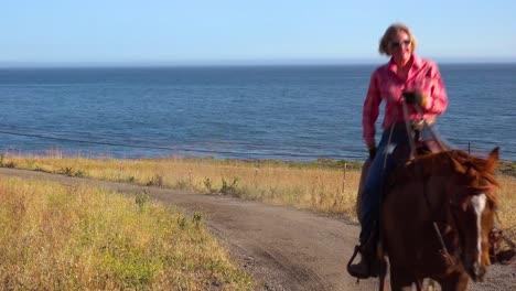 A-Woman-Cowgirl-Gallops-On-Her-Horse-Along-The-Pacific-Ocean-Near-Santa-Barbara-California