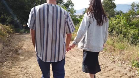 A-Man-And-Woman-Walk-Hand-In-Hand-With-Their-Dog-In-The-Mountains-Of-California-In-Slow-Motion-1