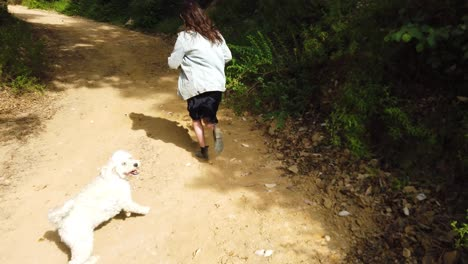 A-Man-Chases-A-Woman-Up-A-Hill-With-Their-Dog-Hiking-In-The-Mountains-Of-California-In-Slow-Motion