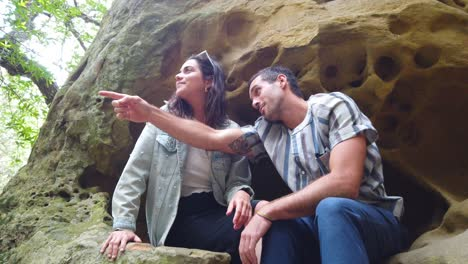 A-Man-And-Woman-Sit-In-A-Rock-Cave-And-Admire-The-Scenery-In-A-Forest-In-Slow-Motion