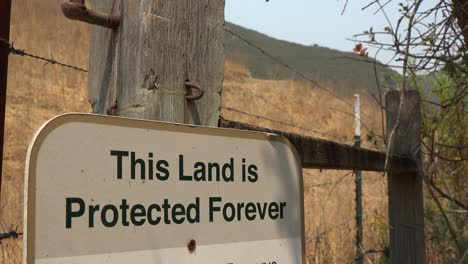 A-Sign-Says-This-Land-Is-Protected-Forever-Suggesting-Conservation-And-Environmentalism