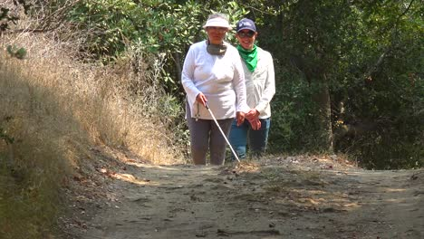 A-Blind-Woman-Walks-With-A-Cane-Through-A-Natural-Area-With-A-Guide-Helping-Her-Explore-The-Wilderness-1