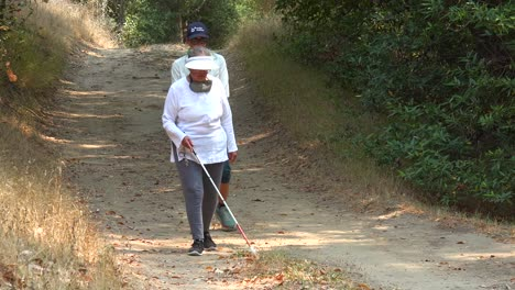 A-Blind-Woman-Walks-With-A-Cane-Through-A-Natural-Area-With-A-Guide-Helping-Her-Explore-The-Wilderness-2