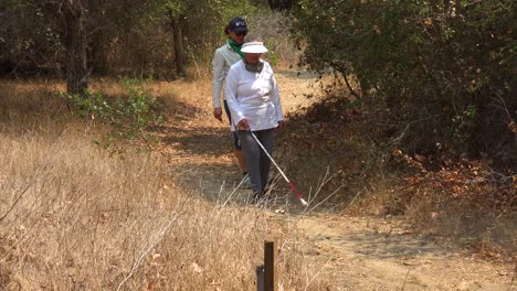 A-Blind-Woman-Walks-With-A-Cane-Through-A-Natural-Area-With-A-Guide-Helping-Her-Explore-The-Wilderness-4