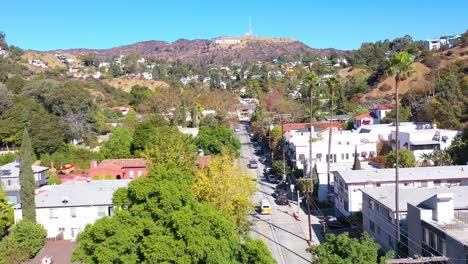 Aerial-Above-Beachwood-Drive-In-Hollywood-With-Cars-Driving-Up-Towards-Hollywood-Sign