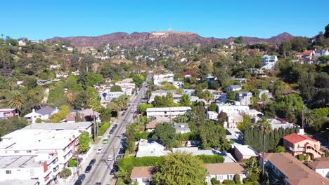 Aerial-Above-Beachwood-Drive-In-Hollywood-With-Cars-Driving-Up-Towards-Hollywood-Sign-1