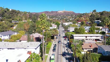 Aerial-Above-Beachwood-Drive-Palms-In-Hollywood-With-Cars-Driving-Up-Towards-Hollywood-Sign