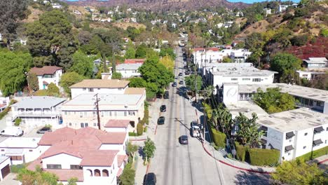 Aerial-Tilt-Up-Reveal-Beachwood-Drive-In-Hollywood-With-Cars-Driving-Up-Towards-Hollywood-Sign