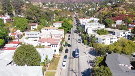 Aerial-Tilt-Up-Reveal-Beachwood-Drive-In-Hollywood-With-Bus-Driving-Up-Towards-Hollywood-Sign