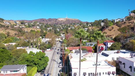Antena-Encima-De-Beachwood-Drive-En-Hollywood-Con-Coches-Y-Autobuses-Conduciendo-Hacia-El-Cartel-De-Hollywood