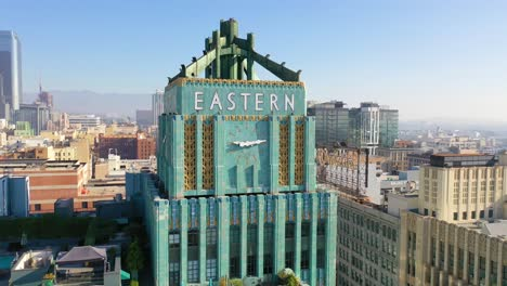 Aerial-Of-The-Historic-Eastern-Building-In-Downtown-Los-Angeles-With-Clock-And-Downtown-City-Skyline-Behind