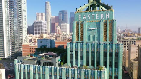 Aerial-Of-The-Historic-Eastern-Building-In-Downtown-Los-Angeles-With-Clock-And-Downtown-City-Skyline-Behind-1