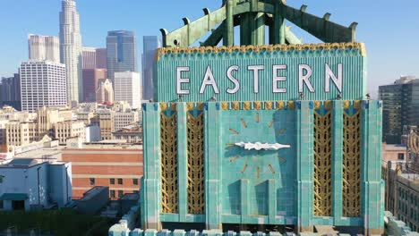 Aerial-Of-The-Historic-Eastern-Building-In-Downtown-Los-Angeles-With-Clock-And-Downtown-City-Skyline-Behind-2