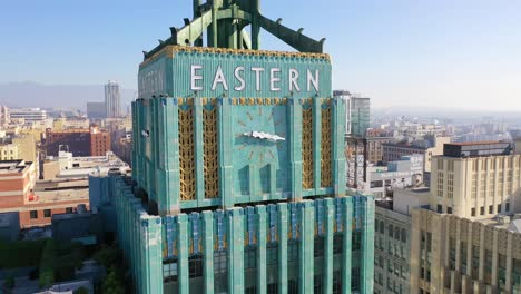 Aerial-Of-The-Historic-Eastern-Building-In-Downtown-Los-Angeles-With-Clock-And-Downtown-City-Skyline-Behind-3