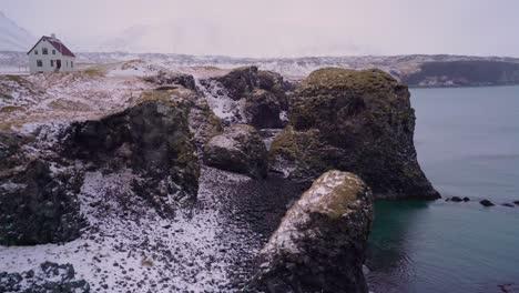 Se-Ve-Una-Casa-Con-Vistas-Al-Puerto-De-Arnarstapi-En-La-Península-De-Snaefellsne-En-Islandia-Con-Nieve-En-El-Suelo