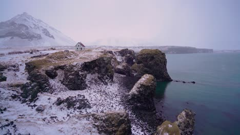 A-house-is-seen-overlooking-Arnarstapi-Harbor-on-the-Snaefellsne-Peninsula-of-Iceland-with-snow-on-the-ground-1
