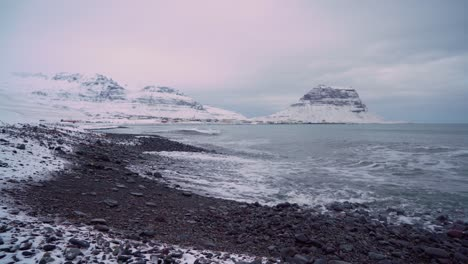 A-rock-harbor-is-seen-with-snowy-town-of-Grundarfjordur-Iceland-in-the-background