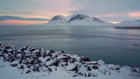 Los-Bancos-Nevados-Se-Ven-En-La-Península-De-Snaefellsne-En-Islandia-Al-Atardecer-Con-Pájaros-Nadando-En-El-Agua