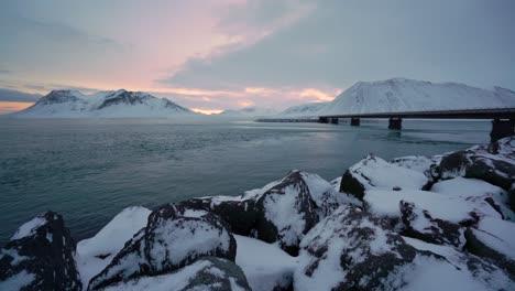 Los-Bancos-Nevados-Se-Ven-En-La-Península-De-Snaefellsne-En-Islandia-Al-Atardecer-Con-Pájaros-Nadando-En-El-Agua-1