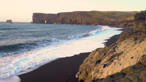 Waves-lap-at-the-black-sand-beach-near-the-rock-arch-of-Dyrholaey-Iceland