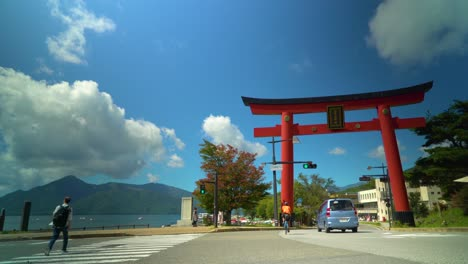 Vehicular-and-foot-traffic-pass-by-a-traditional-red-gate-at-Chuzenji-Lake-in-Nikko-Japan