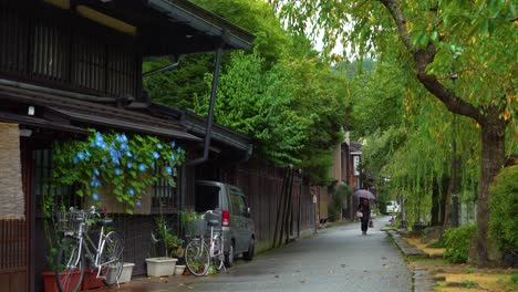 A-woman-walks-along-a-rainy-street-in-Sanmanchi-Suji-in-Takayama-Japan
