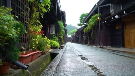 A-rainy-Sanmanchi-Suji-street-is-seen-in-Takayama-Japan-and-rainwater-fills-a-gutter