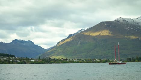 A-boat-is-seen-anchored-in-Lake-Wakatipu-with-mountains-in-full-view-in-Queenstown-New-Zealand