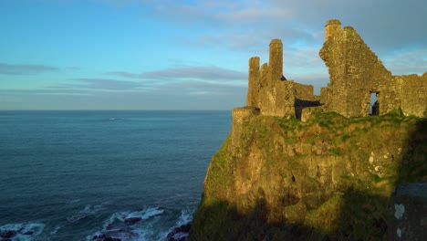 Dunluce-Castle-is-seen-perched-on-a-cliff-by-the-water-in-Antrim-County-Northern-Ireland