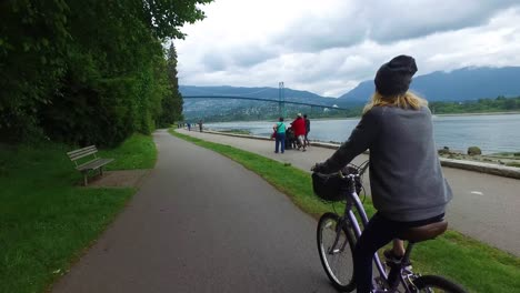 A-bikemounted-camera-captures-the-view-from-behind-as-a-woman-bicycles-along-the-Seawall-at-Stanley-Park-in-Vancouver