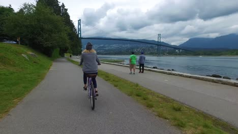 A-bikemounted-camera-captures-the-view-from-behind-as-a-woman-bicycles-along-the-Seawall-at-Stanley-Park-in-Vancouver-1