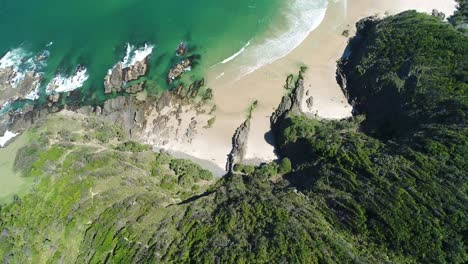 An-Aerial-View-Shows-The-Forested-Cliffside-By-Whites-Beach-In-Byron-S-Bay-Australia