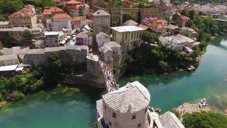 Una-Vista-Aérea-Muestra-Multitudes-Reunidas-En-El-Puente-De-Mostar-Y-El-Río-Neretva-Que-Pasa-Sobre-Mostar-Bosnia-