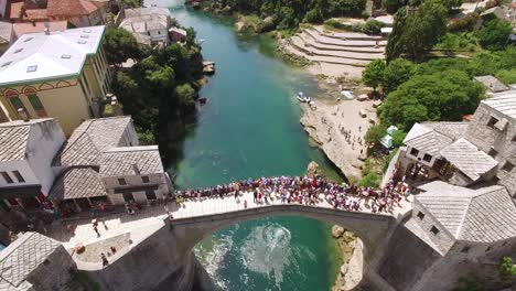 A-Bird-Seyeview-Shows-Crowds-Assembled-On-The-Mostar-Bridge-And-The-Neretva-River-It-Passes-Over-In-Mostar-Bosnia
