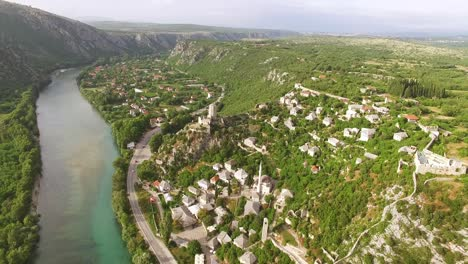 An-Aerial-View-Shows-Cars-Driving-On-The-Road-Between-The-Neretva-River-And-The-Village-Of-Pocitelj-Bosnia