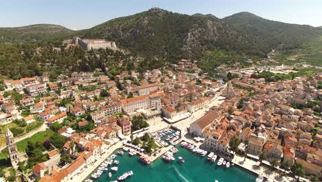 An-Aerial-View-Shows-The-Port-Town-Of-Hvar-Croatia-With-Boats-Docked-In-The-Harbor