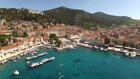 An-Aerial-View-Shows-Sailboats-Approaching-The-Port-Of-Hvar-Croatia