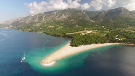 An-Aerial-View-Shows-Zlatni-Rat-Beach-And-Its-Surrounding-Mountains-On-Brac-Island-Croatia