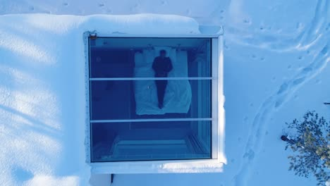 A-Bird\-Seyeview-Zooms-Out-From-A-Man-Resting-In-Bed-At-The-Northern-Lights-Ranch-Revealing-The-Snowy-Landscape-That-Surrounds-His-Lodgings