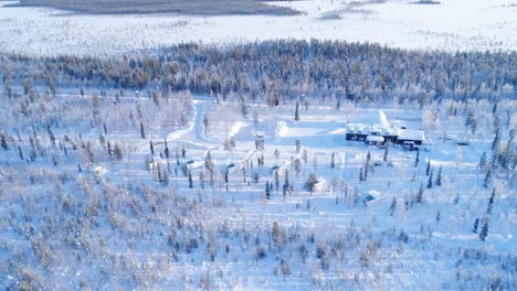 An-Vista-Aérea-View-Shows-Trees-And-Lodgings-Of-The-Snowcovered-Northern-Lights-Ranch-In-Kongas-Finland-3