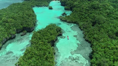 An-Aerial-View-Shows-A-Boat-Moving-Down-A-Waterway-In-Baer-Island-Indonesia