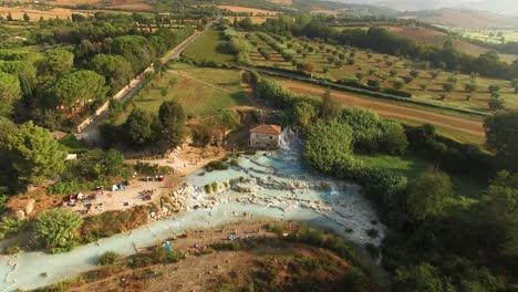Una-Vista-Aérea-Muestra-A-Los-Turistas-Disfrutando-De-Una-Laguna-En-Saturnia-Italia