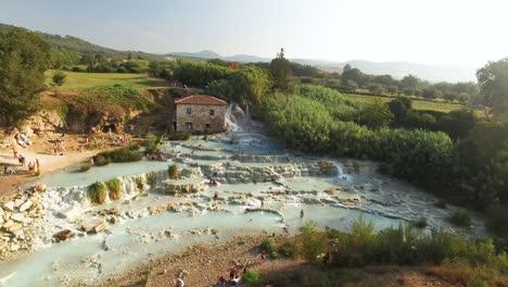 Una-Vista-Aérea-Muestra-A-Los-Turistas-Disfrutando-De-Una-Laguna-En-Saturnia-Italia-1