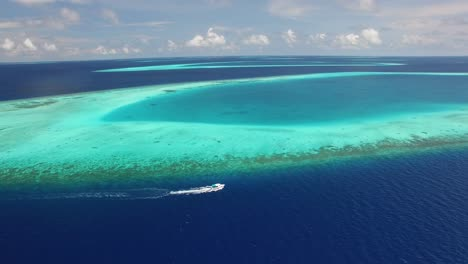 An-Aerial-View-Shows-A-Motorboat-Coasting-Alongside-A-Reef-In-Maldives