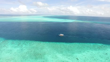 An-Aerial-View-Shows-A-Motorboat-Coasting-Alongside-A-Reef-In-Maldives-1