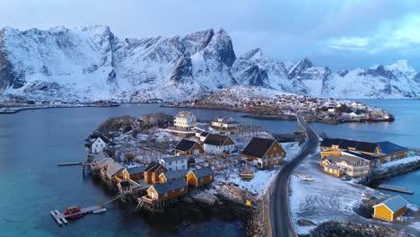Una-Ciudad-En-Las-Islas-Lofoten-Noruega-Se-Ve-Con-Montañas-Cubiertas-De-Nieve-En-La-Distancia